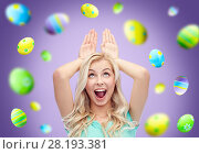 Купить «happy woman making bunny ears over easter eggs», фото № 28193381, снято 13 февраля 2016 г. (c) Syda Productions / Фотобанк Лори
