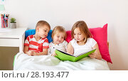 Купить «little kids reading book in bed at home», фото № 28193477, снято 15 октября 2017 г. (c) Syda Productions / Фотобанк Лори
