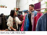 Купить «happy couple at vintage clothing store hanger», фото № 28193525, снято 30 ноября 2017 г. (c) Syda Productions / Фотобанк Лори