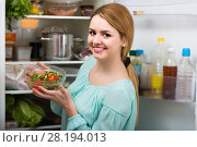 long-haired woman arranging space in fridge at home. Стоковое фото, фотограф Яков Филимонов / Фотобанк Лори