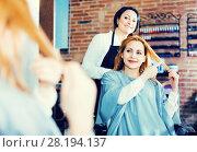 Купить «Woman points to master in hairdress salon right hair length for haircut», фото № 28194137, снято 7 марта 2017 г. (c) Яков Филимонов / Фотобанк Лори