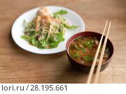 Купить «A bowl of spicy Miso soup and a plate of vegetable salad in a Japanese vegan restaurant, food still life on a wooden table. Kyoto, Japan.», фото № 28195661, снято 20 ноября 2017 г. (c) age Fotostock / Фотобанк Лори