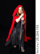 Купить «Red-haired woman wearing in a black long dress and red cloak with hood sits with knightly longsword in her hands, on dark background», фото № 28204193, снято 6 июля 2017 г. (c) Сергей Дубров / Фотобанк Лори