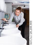 Smiling female buyer choosing ceramic washbasin in store. Стоковое фото, фотограф Яков Филимонов / Фотобанк Лори