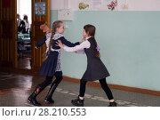 Купить «Две девочки в парадной форме, дерутся в коридоре школы, на фоне класса», фото № 28210553, снято 22 марта 2018 г. (c) Светлана Попова / Фотобанк Лори