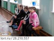 Купить «Девочки сидят на скамейке в школьном коридоре», фото № 28210557, снято 22 марта 2018 г. (c) Светлана Попова / Фотобанк Лори