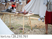 Купить «MOSCOW - JUN 06, 2015: Helmet and swords of Roman soldiers on a wooden table in the camp at the festival Times and epoch: Ancient Rome in Kolomenskoye», фото № 28210761, снято 6 июня 2015 г. (c) Losevsky Pavel / Фотобанк Лори