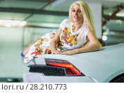 Купить «Young blonde woman in flowery dress lies on hood of modern white car at underground parking», фото № 28210773, снято 2 июня 2016 г. (c) Losevsky Pavel / Фотобанк Лори