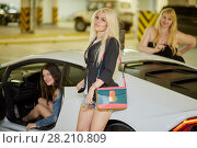 Купить «Three young women in and around modern white car at underground parking», фото № 28210809, снято 2 июня 2016 г. (c) Losevsky Pavel / Фотобанк Лори