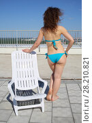 Купить «Woman with curly hair in a blue swimsuit near a white lounger on the roof of a multistory building, view from the back», фото № 28210821, снято 8 июня 2015 г. (c) Losevsky Pavel / Фотобанк Лори