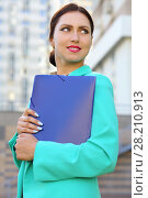 Купить «Business woman in turquoise jacket with blue folder in front of multistory building», фото № 28210913, снято 8 июня 2015 г. (c) Losevsky Pavel / Фотобанк Лори