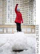 Купить «Happy girl in red raises arm on large snowball near buidling at winter day», фото № 28210933, снято 31 января 2016 г. (c) Losevsky Pavel / Фотобанк Лори