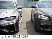 Купить «MOSCOW - JUN 19, 2016: Two sport model car BMW silver colored standing near the glass building», фото № 28211029, снято 19 июня 2016 г. (c) Losevsky Pavel / Фотобанк Лори