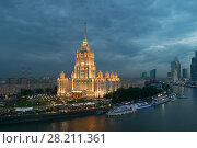 Купить «MOSCOW - MAY 22, 2015: Illuminated Royal Hotel Radisson (Hotel Ukraina) near river at evening, Central volume of building includes 34 floors, Total area of over 88 thousand square meters, height - 206 m, including a 73-meter spire», фото № 28211361, снято 22 мая 2015 г. (c) Losevsky Pavel / Фотобанк Лори