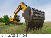 Купить «Big yellow excavator in green field at summer day, closeup of excavator bucket», фото № 28211369, снято 19 августа 2015 г. (c) Losevsky Pavel / Фотобанк Лори