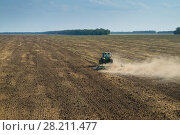 Купить «KRASNODAR REGION, RUSSIA - AUG 19, 2015: Modern green tractor plows field after harvesting, In 2015 in Krasnodar region yields reached record level - 58.4 centners per hectar», фото № 28211477, снято 19 августа 2015 г. (c) Losevsky Pavel / Фотобанк Лори