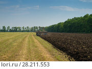 Купить «KRASNODAR REGION, RUSSIA - JUL 7, 2015: Modern tractor plow field after harvest, In 2015 in Krasnodar region have collected record grain harvest - 102 million tons of grain», фото № 28211553, снято 7 июля 2015 г. (c) Losevsky Pavel / Фотобанк Лори