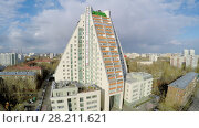 Купить «MOSCOW - APR 21, 2015: Dwelling complex Pyramid with commercial banner of fitness center with pool at spring sunny day. Aerial view video frame», фото № 28211621, снято 21 апреля 2015 г. (c) Losevsky Pavel / Фотобанк Лори