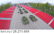 Купить «SAMARA - MAY 06, 2015: Military motorcade with tanks moves along empty tribunes during parade rehearsal at spring evening. Aerial view video frame», фото № 28211669, снято 6 мая 2015 г. (c) Losevsky Pavel / Фотобанк Лори