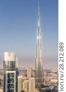 DUBAI, UAE - JAN 9, 2017: Millenium Tower and Burj Khalifa, Burj Khalifa - skyscraper in height of 828 meters in Dubai, tallest structure in world. Редакционное фото, фотограф Losevsky Pavel / Фотобанк Лори