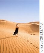 Купить «Woman in black dress goes in on yellow sand in desert, back view», фото № 28212113, снято 12 января 2017 г. (c) Losevsky Pavel / Фотобанк Лори