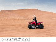 Купить «Young woman in black on ATV among dunes in desert at sunny hot day», фото № 28212293, снято 19 января 2017 г. (c) Losevsky Pavel / Фотобанк Лори