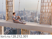 Купить «Roofer sits on concrete cross beam of Cayan Tower (Infinity Tower) in Dubai, UAE», фото № 28212301, снято 20 января 2017 г. (c) Losevsky Pavel / Фотобанк Лори