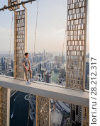 Купить «Roofer poses on concrete cross beam of Cayan Tower (Infinity Tower) in Dubai, UAE», фото № 28212317, снято 20 января 2017 г. (c) Losevsky Pavel / Фотобанк Лори