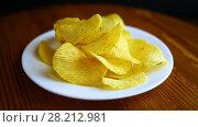Купить «Crispy potato chips in a white plate», видеоролик № 28212981, снято 21 марта 2018 г. (c) Peredniankina / Фотобанк Лори