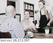 Купить «young waiter girl brought cup of coffee for couple of different aged people», фото № 28213397, снято 22 апреля 2017 г. (c) Яков Филимонов / Фотобанк Лори