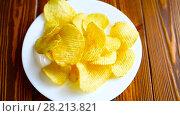 Купить «Crispy potato chips in a white plate», видеоролик № 28213821, снято 12 марта 2018 г. (c) Peredniankina / Фотобанк Лори