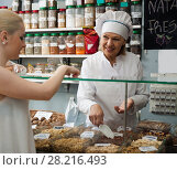 Купить «mature woman offering client different nuts in local supermarket», фото № 28216493, снято 29 января 2016 г. (c) Татьяна Яцевич / Фотобанк Лори