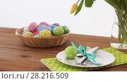 Купить «easter eggs in basket and flowers on served table», видеоролик № 28216509, снято 15 марта 2018 г. (c) Syda Productions / Фотобанк Лори