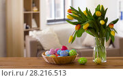 Купить «colored easter eggs in basket and flowers at home», видеоролик № 28216513, снято 15 марта 2018 г. (c) Syda Productions / Фотобанк Лори