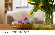 Купить «colored easter eggs in basket and flowers at home», видеоролик № 28216521, снято 15 марта 2018 г. (c) Syda Productions / Фотобанк Лори