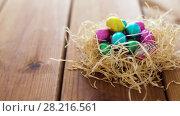 Купить «chocolate easter eggs in straw nest on table», видеоролик № 28216561, снято 16 марта 2018 г. (c) Syda Productions / Фотобанк Лори