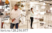 Купить «Smiling couple customers choosing floor lamp with a long standard in store», видеоролик № 28216977, снято 13 февраля 2018 г. (c) Яков Филимонов / Фотобанк Лори