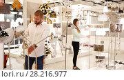 Smiling couple customers choosing floor lamp with a long standard in store. Стоковое видео, видеограф Яков Филимонов / Фотобанк Лори