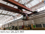 Купить «Overhead cranes with a crane operator cabin and hooks in a multi-span metal frame workshop. Steel landing pad.», фото № 28221981, снято 13 февраля 2018 г. (c) Евгений Ткачёв / Фотобанк Лори