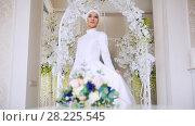Купить «Beautiful bride in white traditional muslim dress with bunch of flowers», видеоролик № 28225545, снято 20 апреля 2018 г. (c) Константин Шишкин / Фотобанк Лори