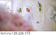 Купить «Beautiful muslim model in white wedding dress with muslim headdress posing in studio», видеоролик № 28226173, снято 27 июня 2019 г. (c) Константин Шишкин / Фотобанк Лори