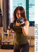 Купить «Woman boxer in time of workout», фото № 28226285, снято 21 марта 2018 г. (c) Владимир Мельников / Фотобанк Лори