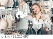 Купить «Smiling female shopper examining bras in shop», фото № 28226697, снято 20 марта 2017 г. (c) Яков Филимонов / Фотобанк Лори