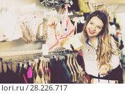 Купить «Female customer deciding on pretty bra», фото № 28226717, снято 20 марта 2017 г. (c) Яков Филимонов / Фотобанк Лори