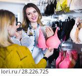 Купить «Female seller demonstrating client bras in underwear store», фото № 28226725, снято 20 марта 2017 г. (c) Яков Филимонов / Фотобанк Лори