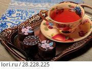 Купить «Конфеты с шоколадной глазурью и чай в красивой чашке», фото № 28228225, снято 22 марта 2018 г. (c) Яна Королёва / Фотобанк Лори