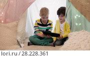 Купить «little boys with tablet pc in kids tent at home», видеоролик № 28228361, снято 23 февраля 2018 г. (c) Syda Productions / Фотобанк Лори