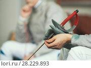Купить «Young fencer in uniform holding rapier in hands», фото № 28229893, снято 26 марта 2018 г. (c) Константин Шишкин / Фотобанк Лори