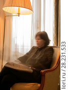 Купить «Woman Sitting in an Armchair and Reading a Newspaper and Illuminated From a Floor Lamp in Motion Blur in Cannes In Provence-Alpes-Côte d'Azur, France», фото № 28231533, снято 23 марта 2019 г. (c) age Fotostock / Фотобанк Лори