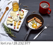 Купить «White wooden board with pieces of different kind of cheese and a round cast-iron frying pan with fried egg and sausages, top view.», фото № 28232977, снято 26 февраля 2018 г. (c) age Fotostock / Фотобанк Лори